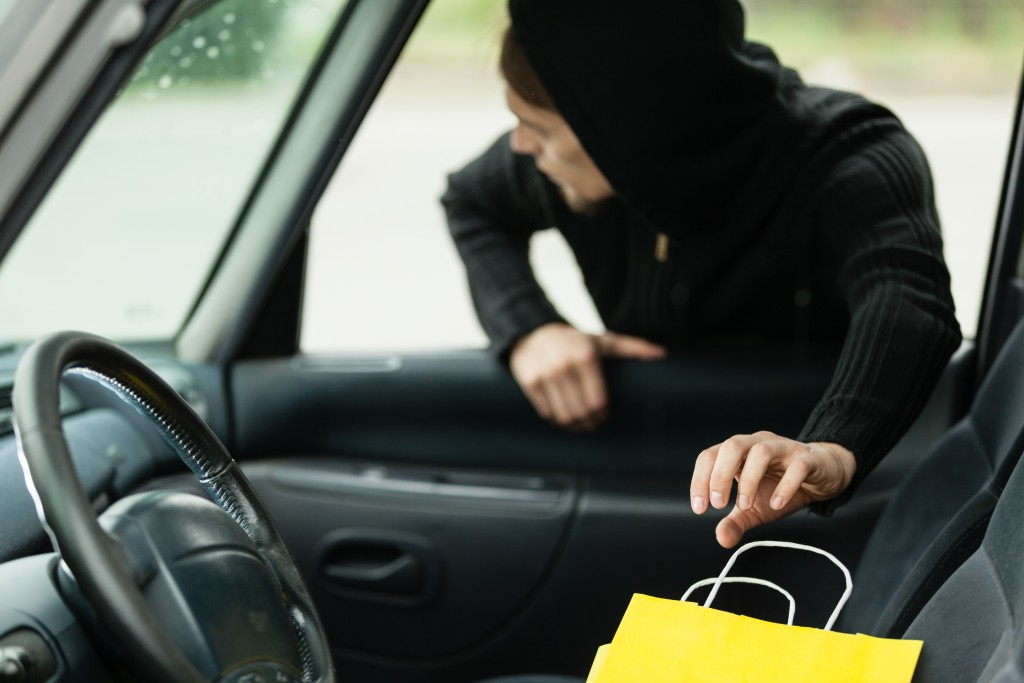 a car thief reaching into the car to steal a valuable item