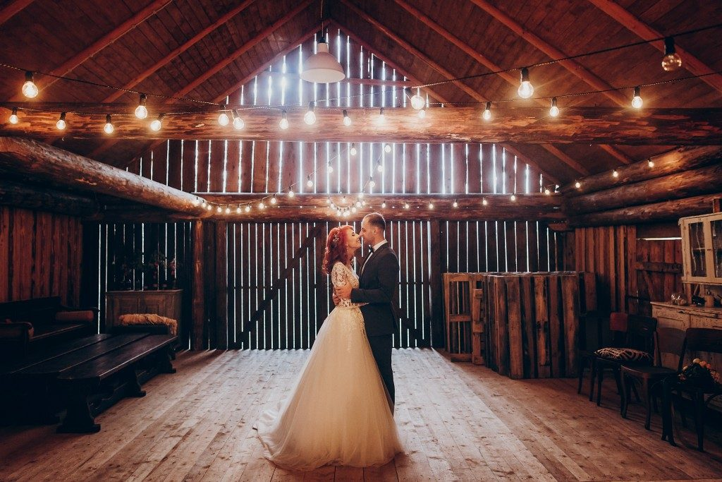 Newly weds hugging in a wooden barn