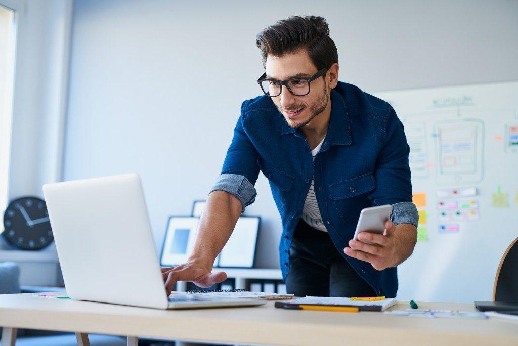 Web designer using laptop and phone