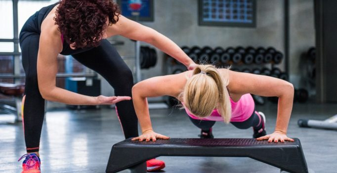 Fitness trainer correcting push up form