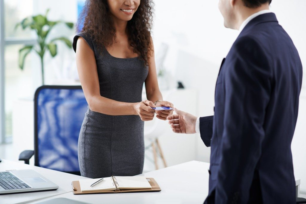 business woman giving business card to a man