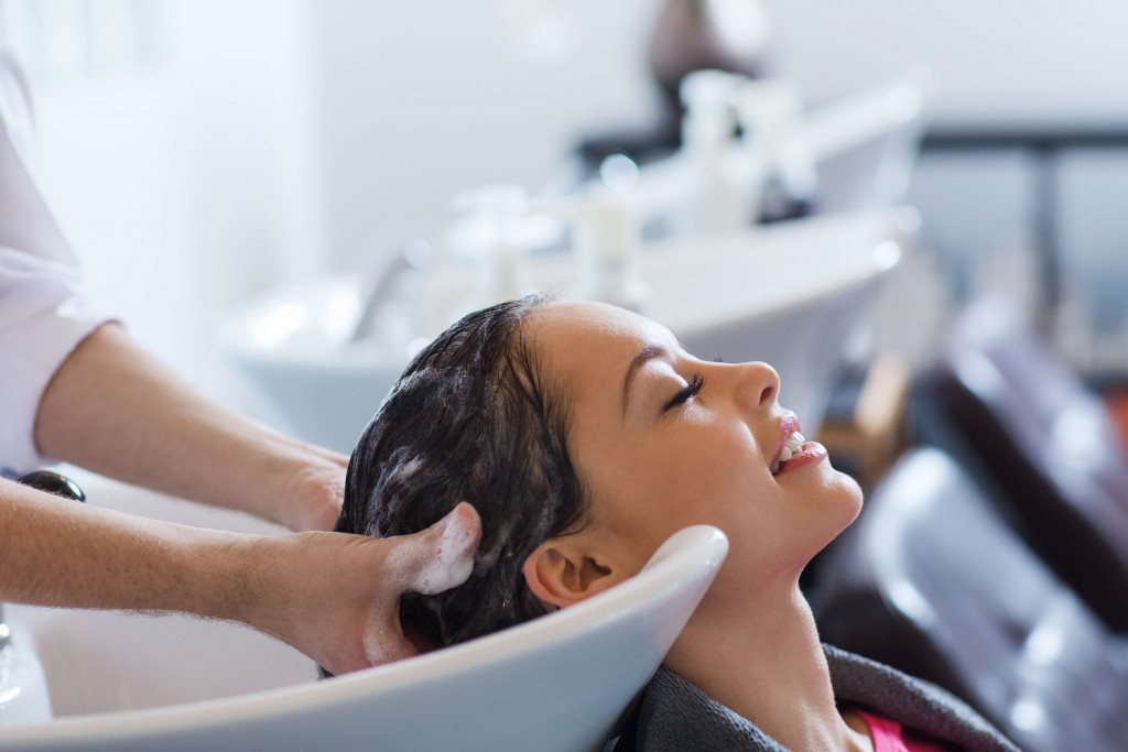 happy young woman with hairdresser washing head