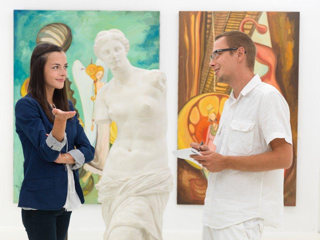 Two people talking in an art gallery