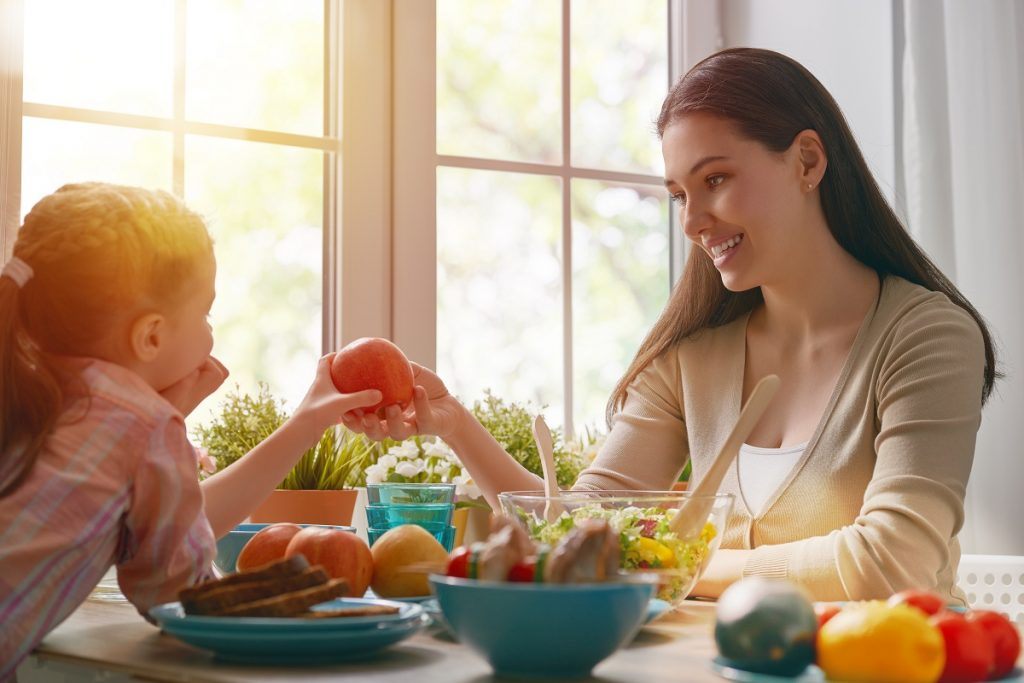 Parent giving apple to child