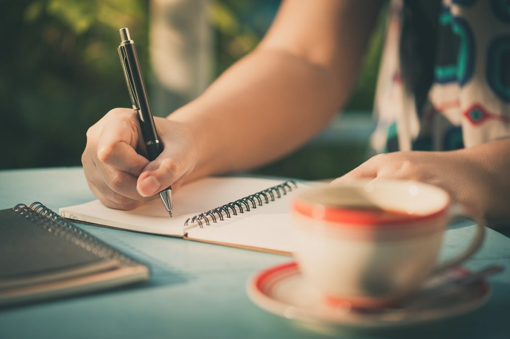 Woman writing on journal