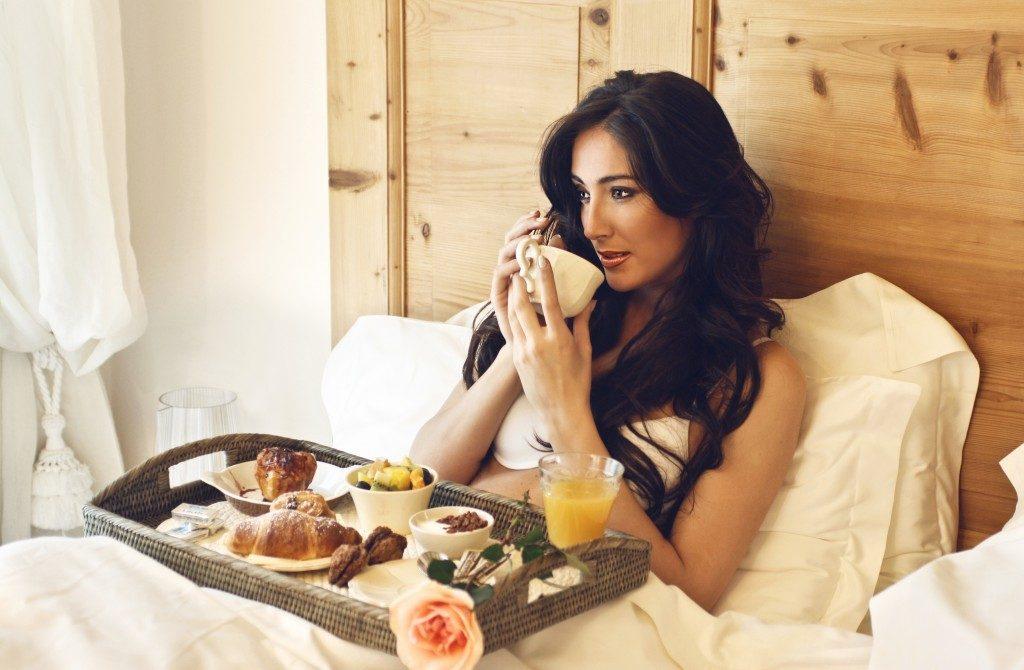 beautiful woman having breakfast in the hotel bed