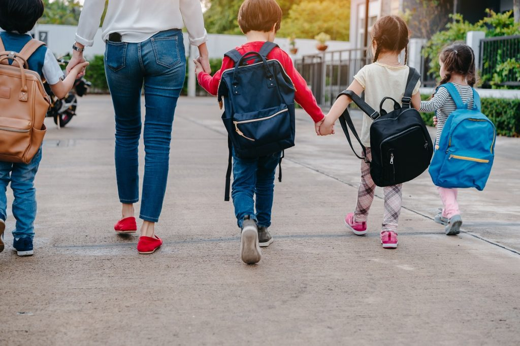 kids wearing backpack walking with a guardian
