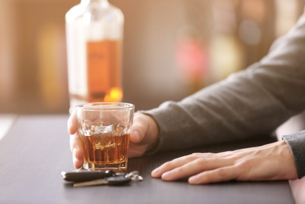 man drinking whiskey in a bar