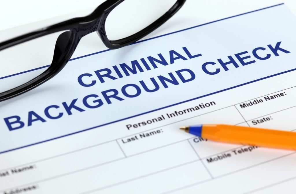 Criminal background check application form with glasses and ballpoint pen