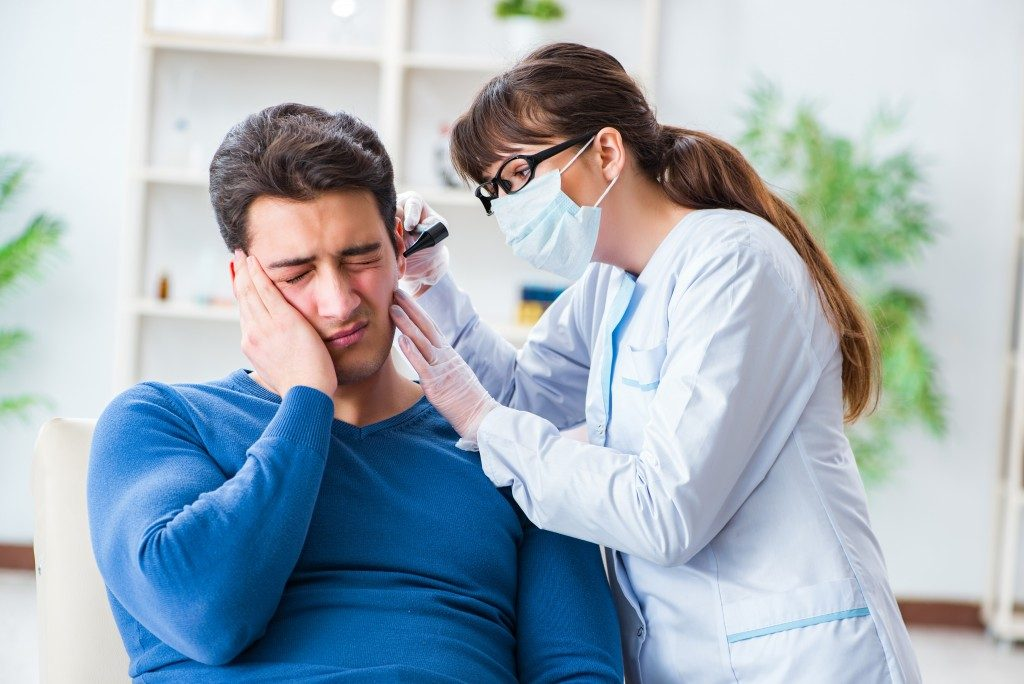 ENT doctor examining the ear of a man