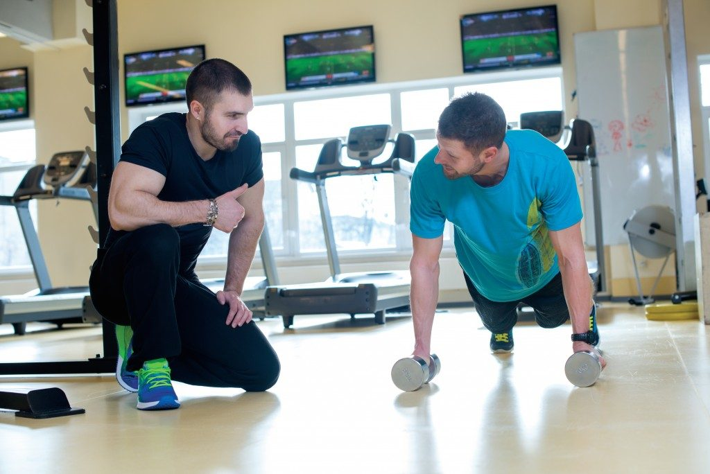 Professional trainer and client in a fitness gym are having training