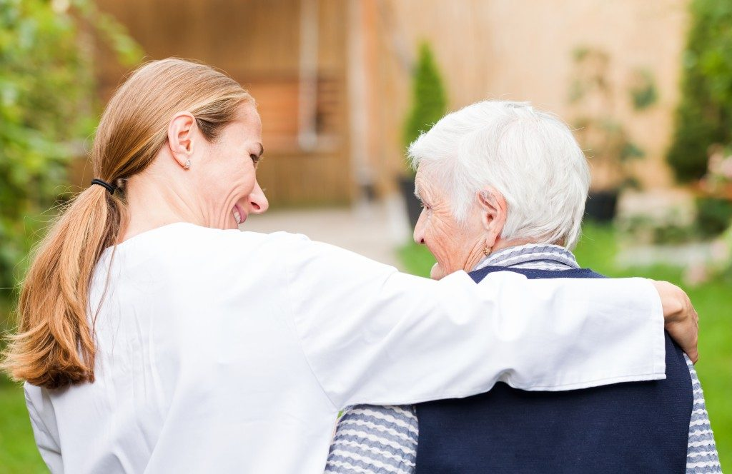 caretaker walking with the elderly woman