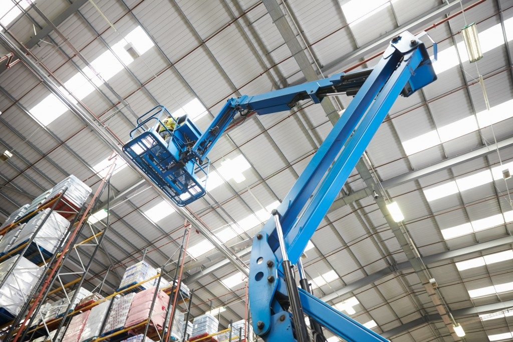 Moving stock in a warehouse with a cherry picker, low angle