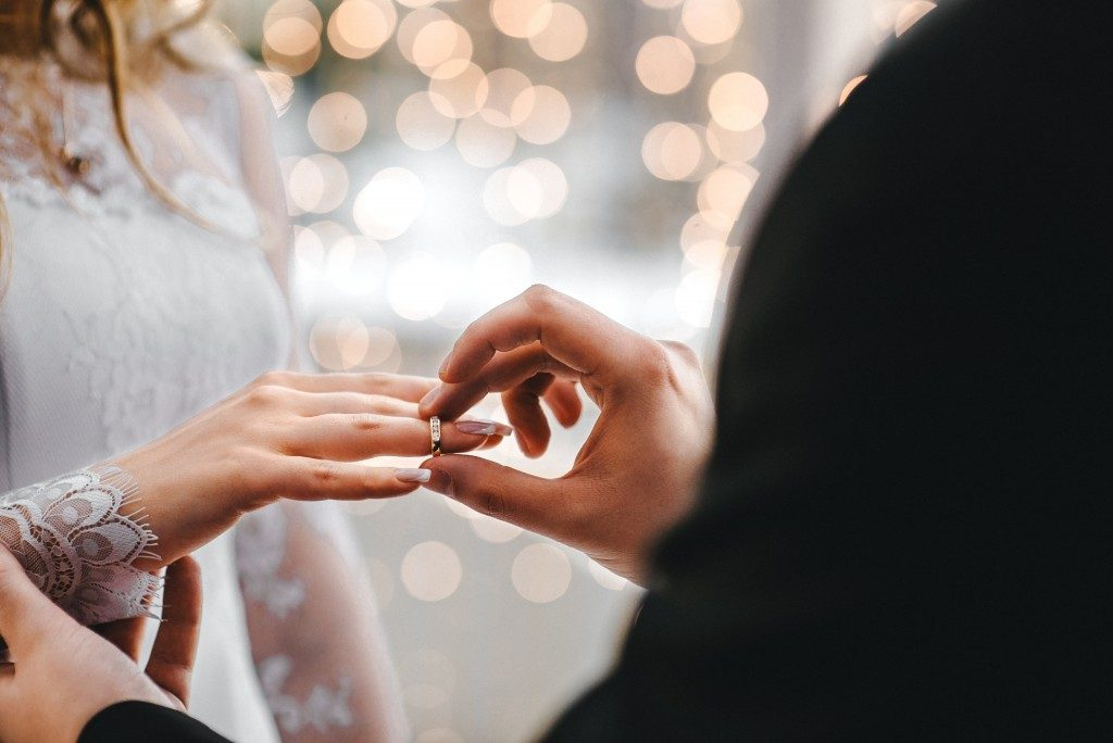 Groom putting wedding ring to bride
