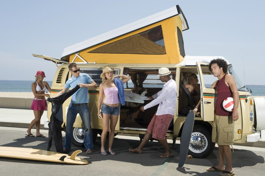 Multiethnic group of young people by campervan