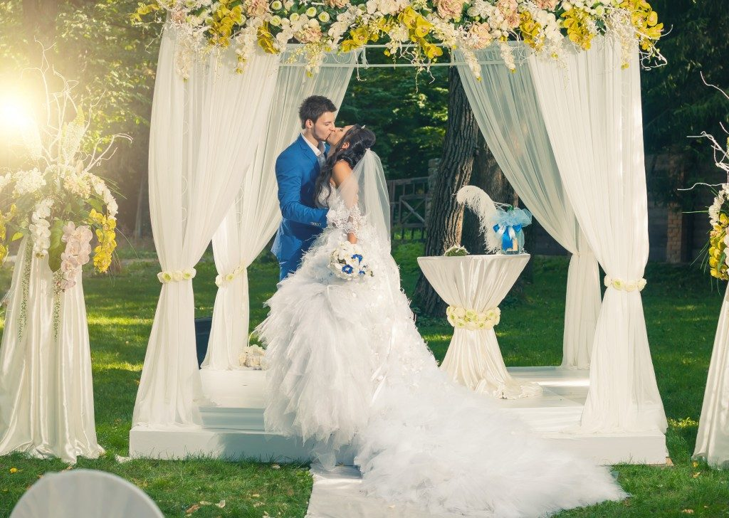 groom and bride kissing inside wedding marquee