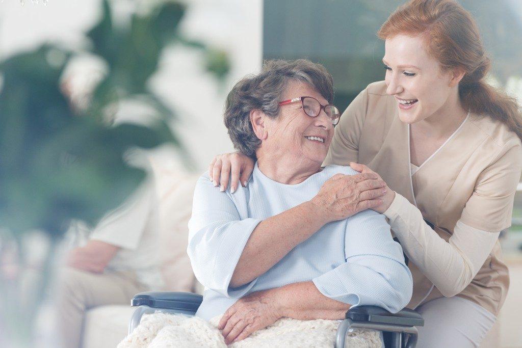 elderly woman in a wheelchair taken care