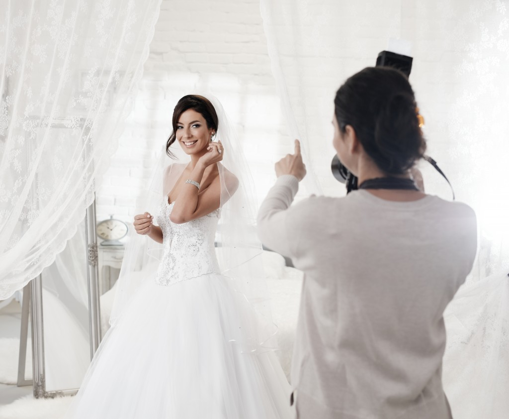 Female photographer photographing beautiful happy bride indoors