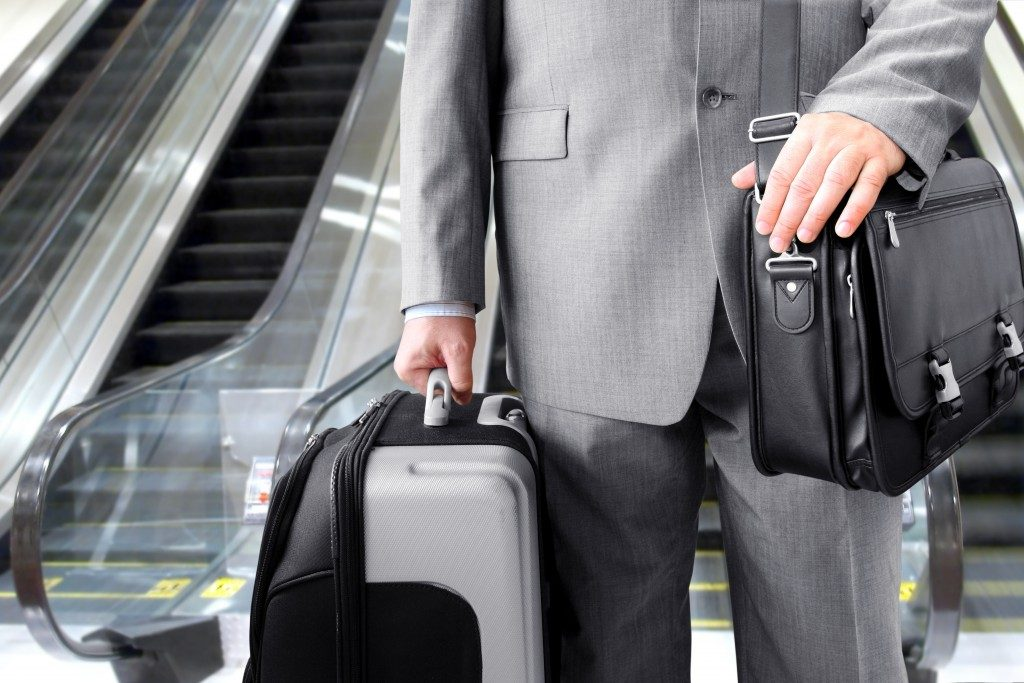 Travelling Businessman. Businessman with his luggage near an escalator at an airport
