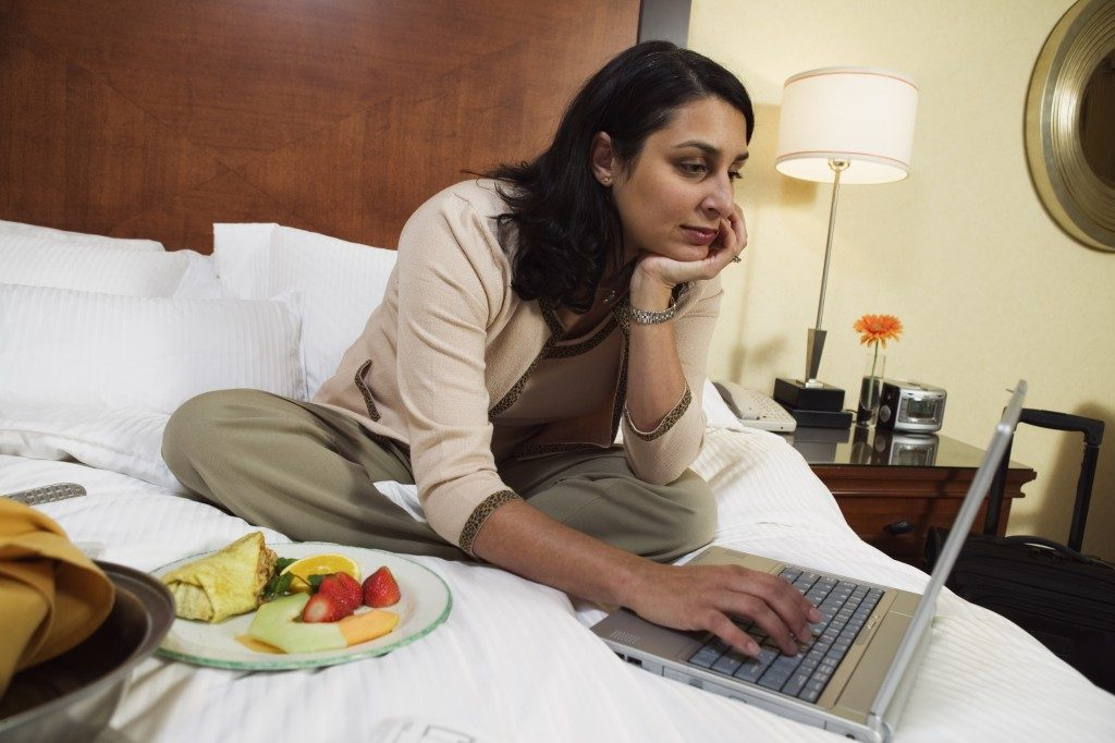 woman working and eating on the bed