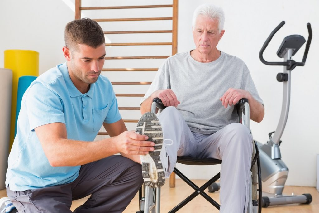 Physical therapist checking an old man
