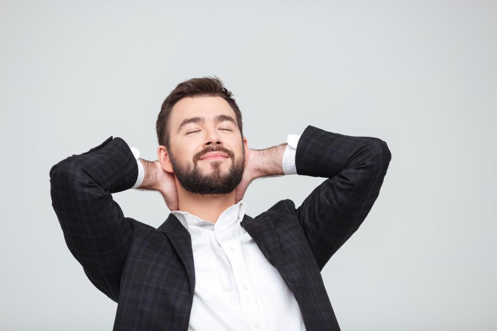 man relaxing hands behind head