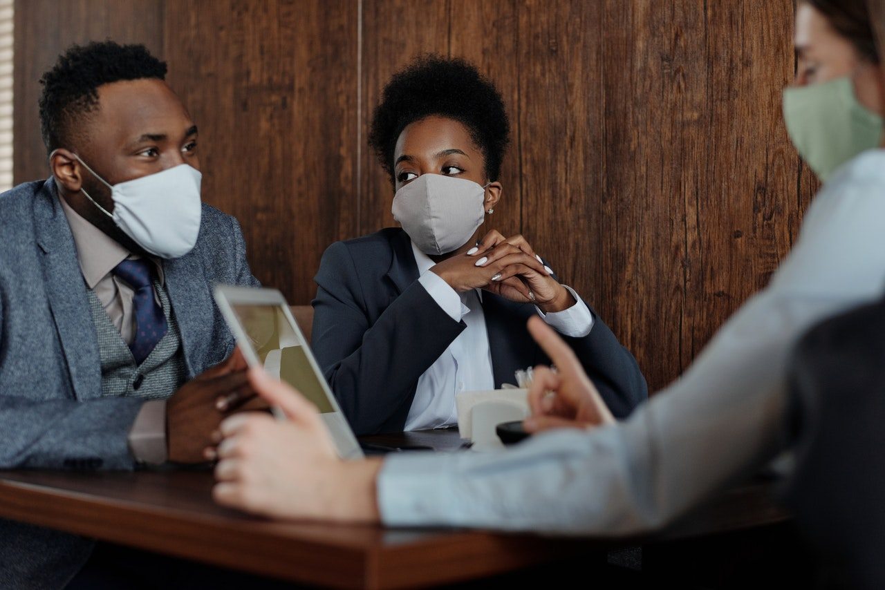 3 people having a meeting while wearing face masks