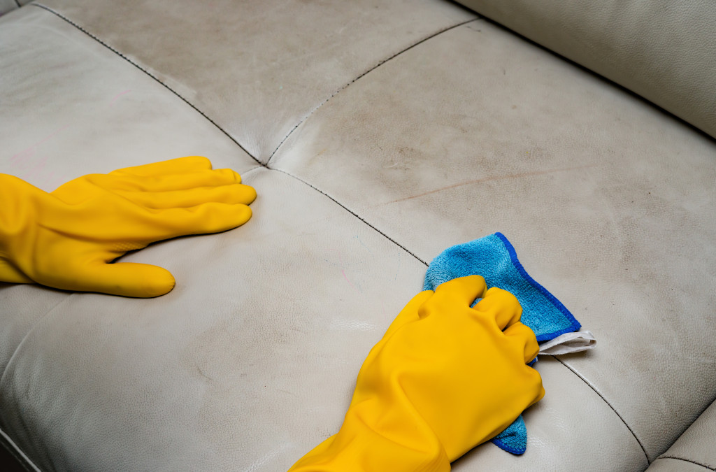 man cleaning leather sofa