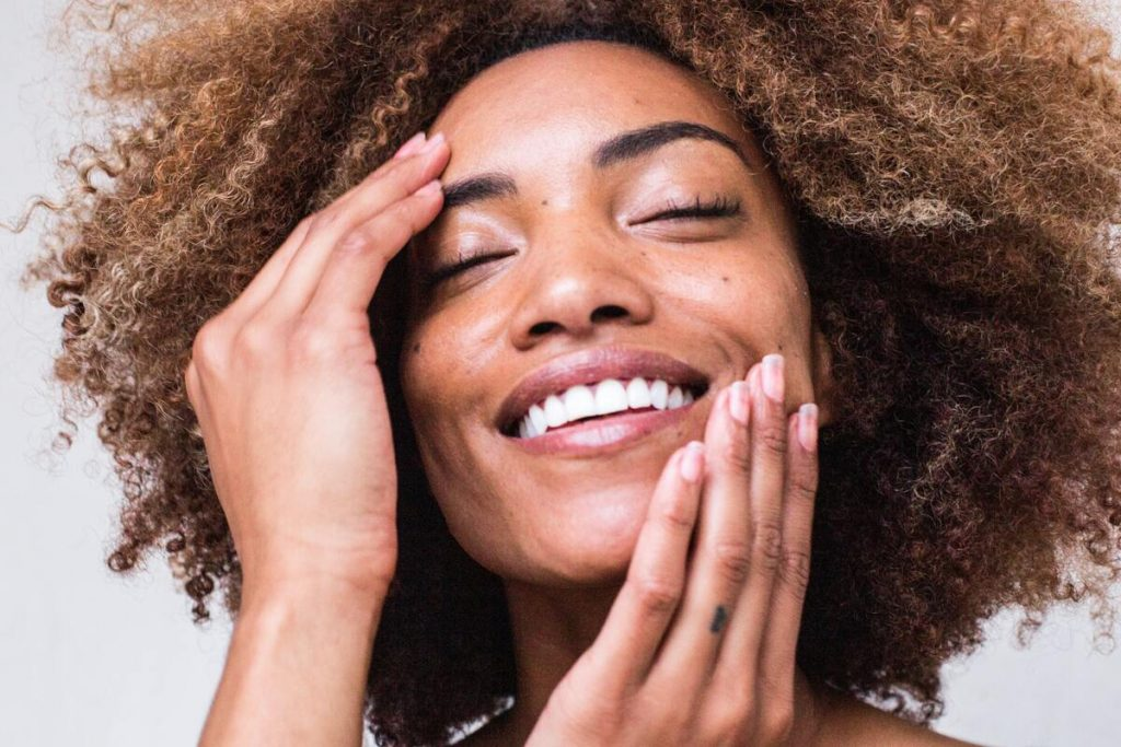 woman smiling while touching her face
