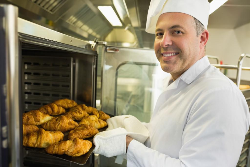 man baking croissants